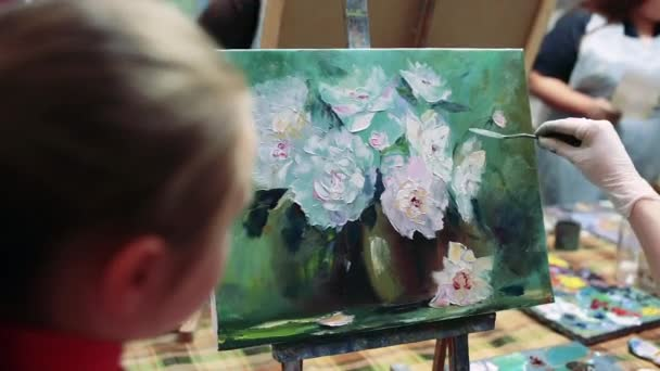 Girl artist painting with oil on easel.