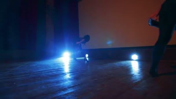 Boky dívky v sexy kostýmech tančí v osvětlené scéně