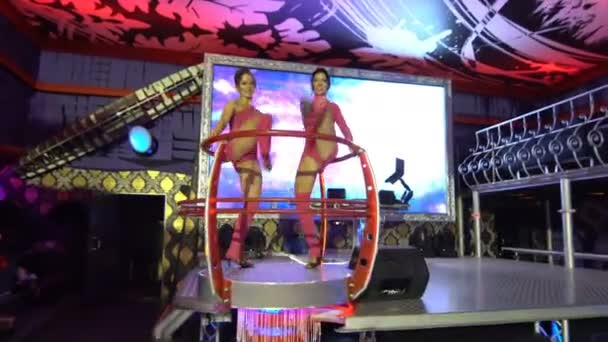 Girls dance at a party in a nightclub with colored lights