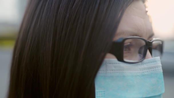 Nahaufnahme eines Mädchens mit Brille und medizinischer Maske.
