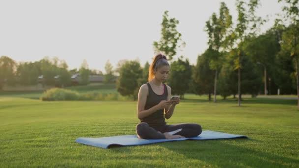 Mladá dívka sedí na zelené trávě po józe, a používá telefon.