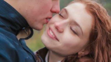 Muž líbá dívku v detailním sníh
