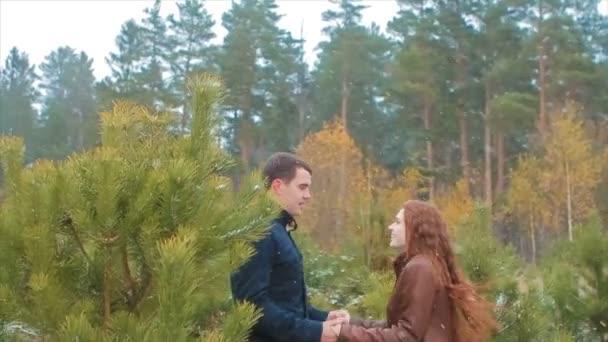 Fiatal pár kézen ugrik az őszi erdő a hóban