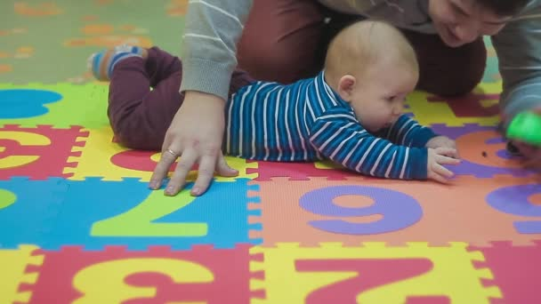 Kid and His Dad Playing With Green Toy on Colored Carpet
