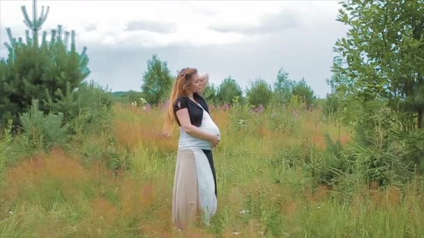 Těhotná mladá matka stojící v poli v létě