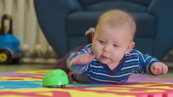 Děťátko hrát s hračkami, na podlaze v pokoji