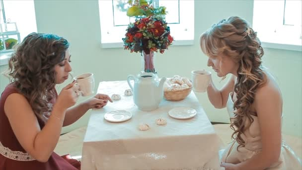 Two Young Friends Drink Tea at Table Slow Motion