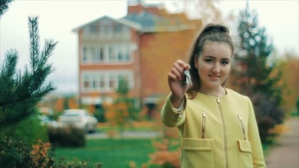 Mladá krásná žena v žluté zobrazeno banda domov klˇźe