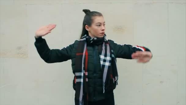 Sexy žena v černém s make-up tancem proti bílé malované zdi
