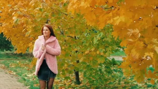 young woman in autumn park in pink walking near maple yellow tree, posing