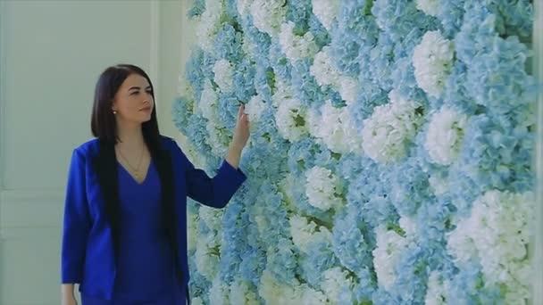 Brünettes Mädchen in Blau läuft neben Blumenmauer in Zeitlupe