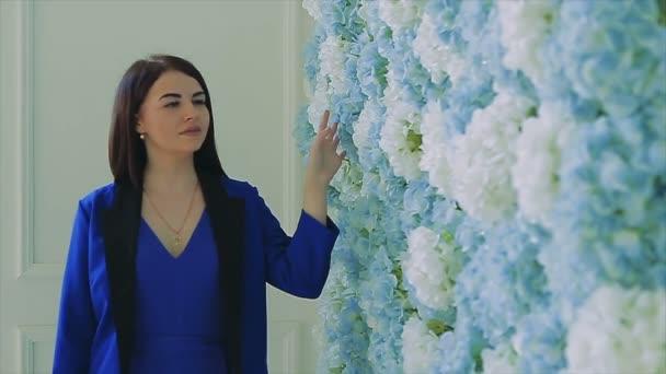 Brünette Mädchen in blau Wandern neben Blume Wand-Slow-motion