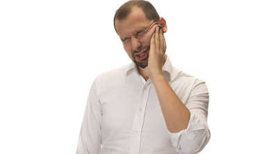 young handsome man with big toothache on white background