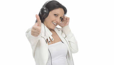 Woman listening music in headphones and showing thumbs up. isolated on white background.