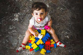 newborn play building blocks - colorful toy bricks - above view of a baby playing with toy bricks - little child play on floor