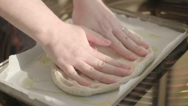 ruce tvořící těsto natáhnout na pekařský list s olivovým olejem - domácí rustikální pizza italská kuchyně timelapse