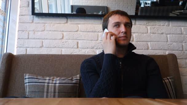 Muž odpovědi telefon v kavárně a Nový Ostružina Bouře smartphone