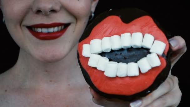 Closeup weibliche rote Lippen Essen Donut und Lächeln