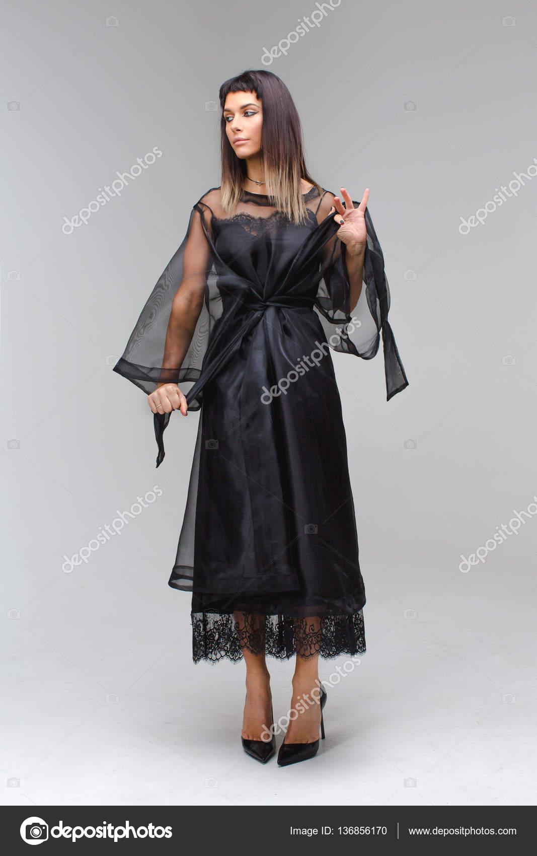 eb47dbea1 Modelo que ata a la cintura y tentador miró lejos al lado de un vestido  vintage negro largo. Mujer en ropa interior sexy vestido transparente y  zapatos ...