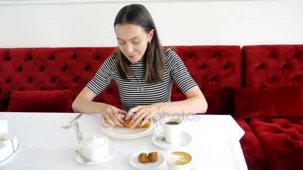 Žena jí šálek kávy snídani croissant