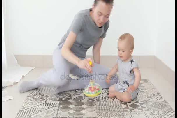 Mother and child boy play together in whirligig