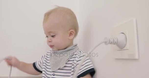 Junge spielt mit Stecker und Steckdose