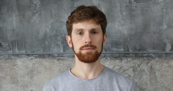 Vörös hajú szakállas fickó egy szürke háttér