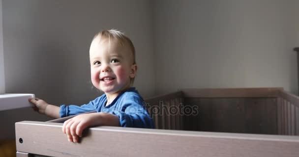 Dítě v postýlce vypadá kolem a usmívá se