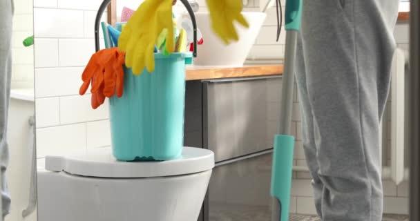 Žena držící mop a vědro s čištěním doma