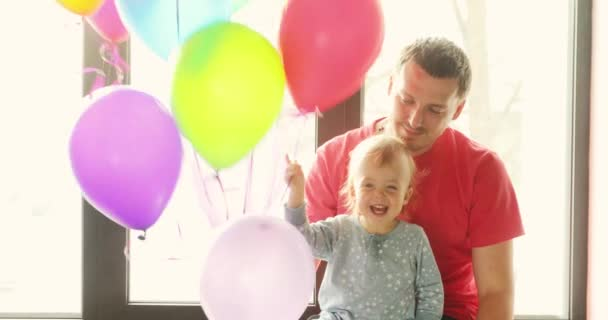 Kid with the daddy and balloons sit on window sill