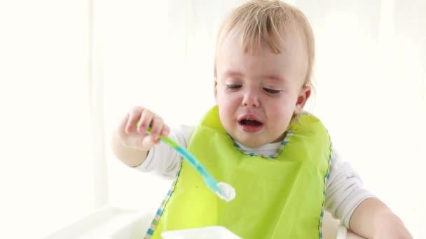 Piccolo neonato che è sconvolto, che tiene cucchiaio con latticini. Il bambino in giovane età è visibilmente triste. Bambino non vuole mangiare seduto su una sedia alta