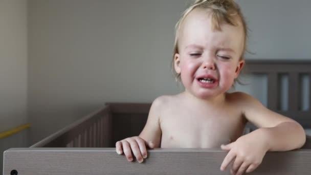 Plačící dítě v postýlce doma