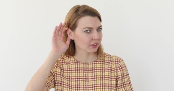 Woman holds hand near ear and listens carefully