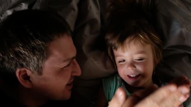 Father with son lie close up portrait