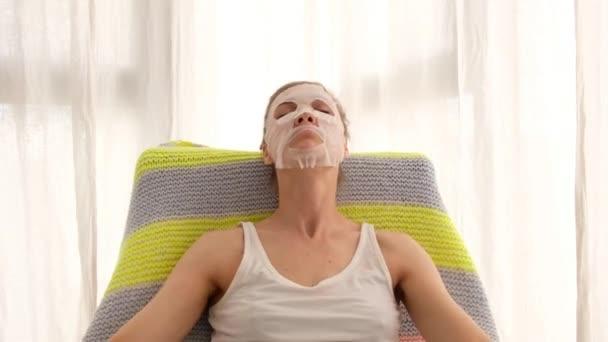 Žena s plátěnou maskou relaxující v křesle