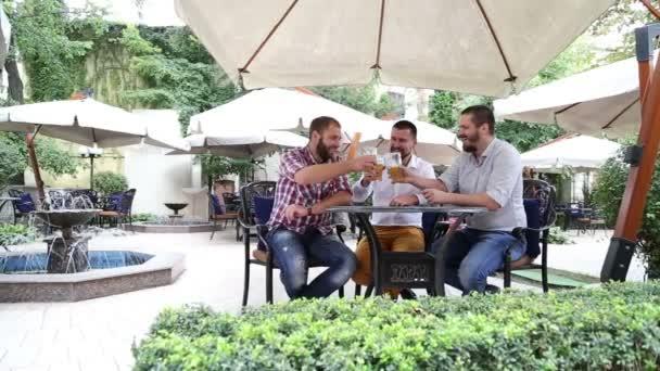 Tre maschi in caffè bere birra leggera