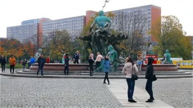Berlin - November 2017: Tourists strolling along Alexanderplatz near the monument to Neptune