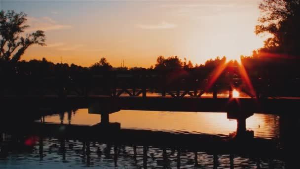 Evening landscape and sunset. People walk along the bridge across the river in the park.