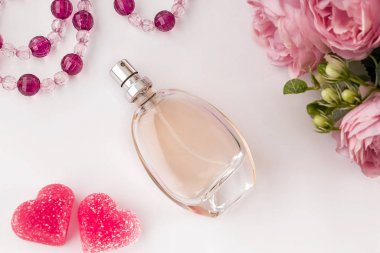 Bottle of perfume, flowers and hearts on a light background. Perfume and roses as a gift for Valentine's Day.