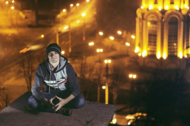 Young man make selfie on roof at night