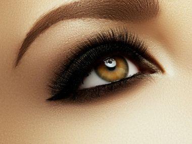 Beautiful macro shot of female eye with extreme long eyelashes and black liner makeup. Perfect shape makeup and long lashes. Cosmetics and make-up. Closeup macro shot of fashion eyes visage
