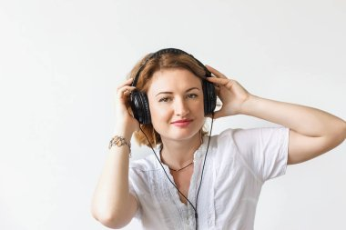 Beautiful girl with headphones listening to music and dancing in