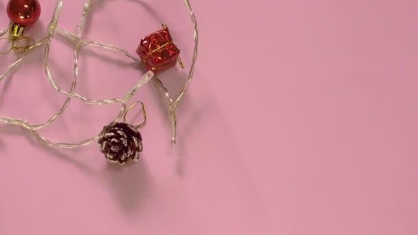 Lichter und Weihnachtsdekoration auf rosa Hintergrund