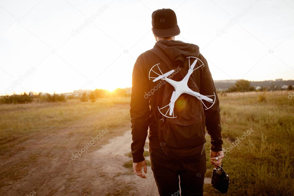 Young man with drone go to sunset, free space