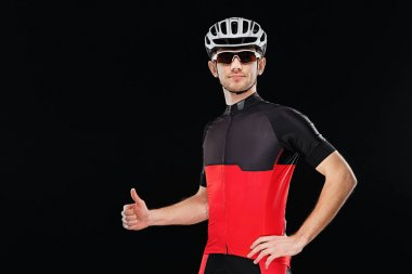 Sport. Cyclist in training clothes, sunglasses and helmet showin