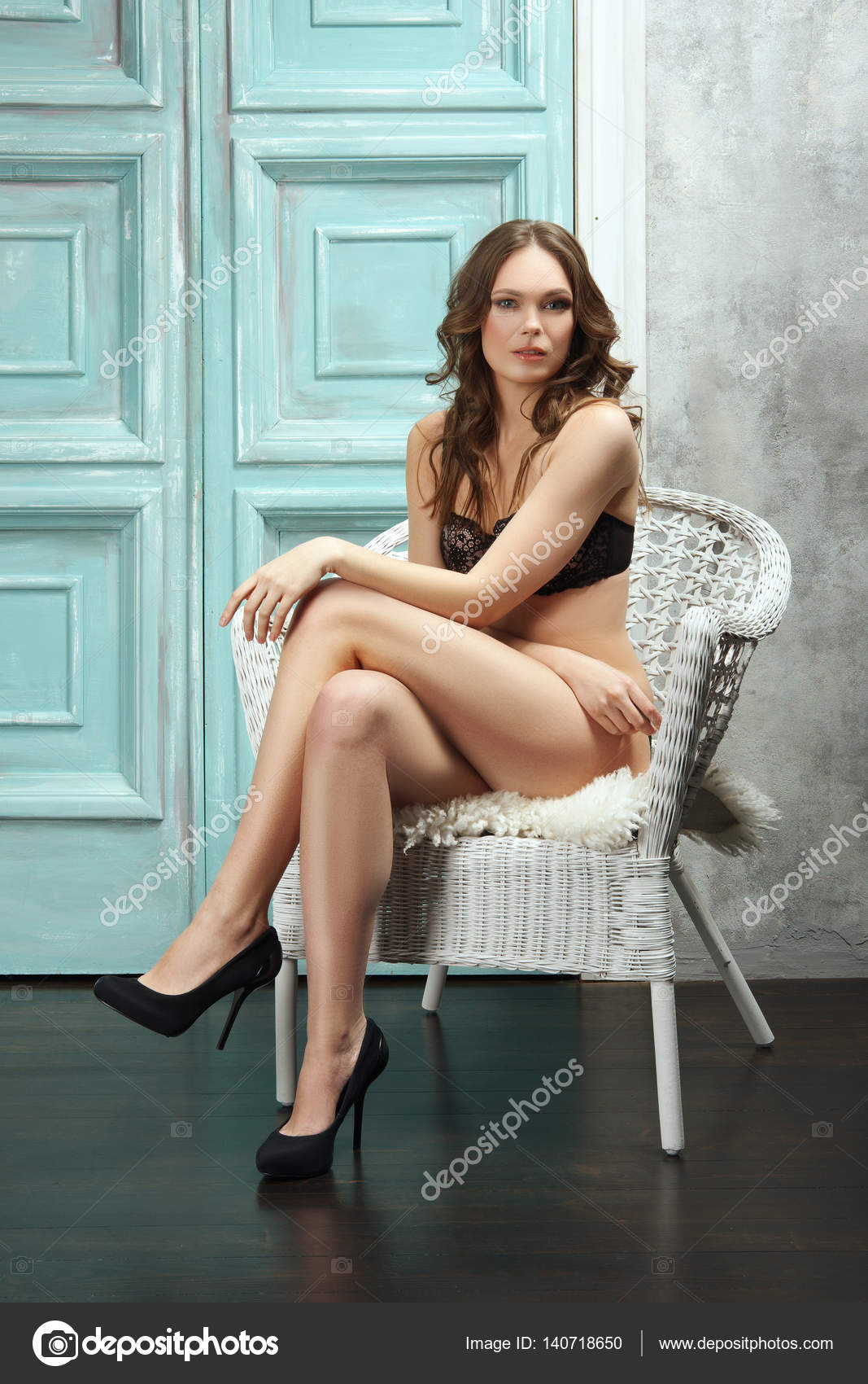 Sexy lady in lingerie sitting in armchair with crossed