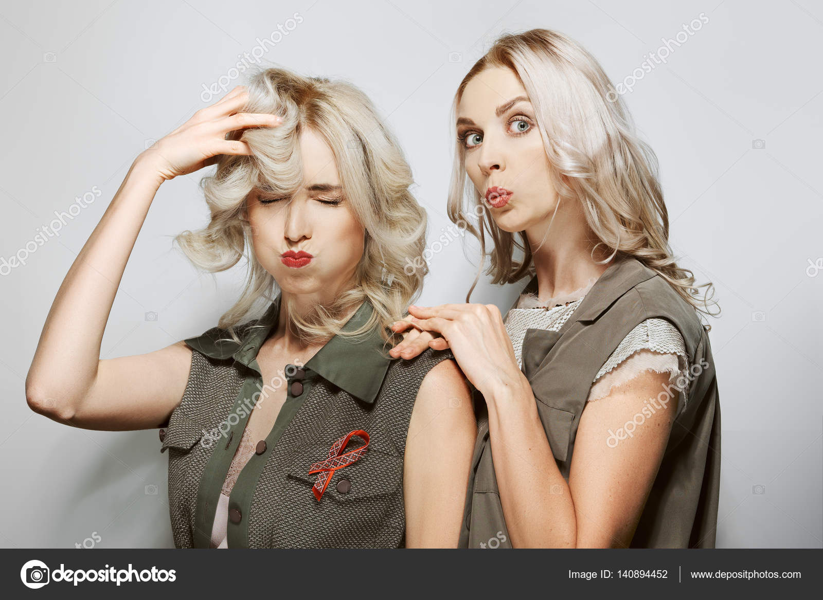 two pretty blonde girls play the ape make faces stock photo