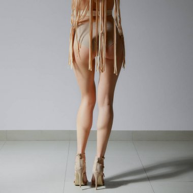 Back view of female legs in shoes with high heels. Seamless ling