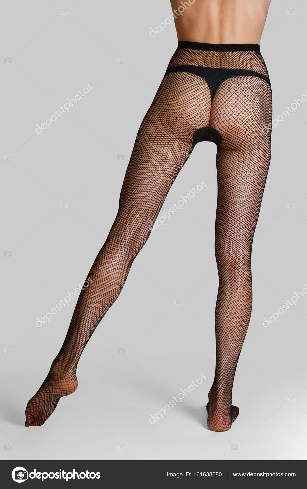 Long Slim Female Legs In Elegant And Sexy Black Fishnet Tights Back View With One