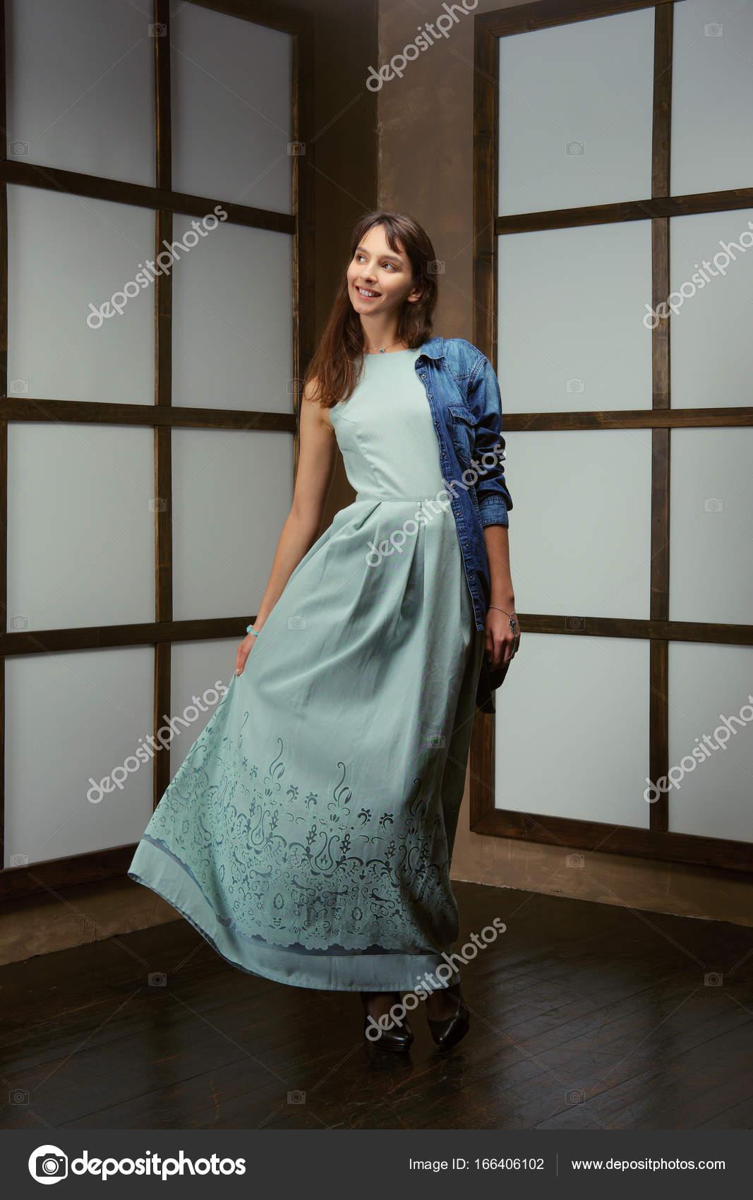 6f9a152b6d35 Αρκετά μοντέλο επιδεικνύοντας στολή - μακρύ βαμβακερό φόρεμα και τζιν  μπουφάν– εικόνα αρχείου